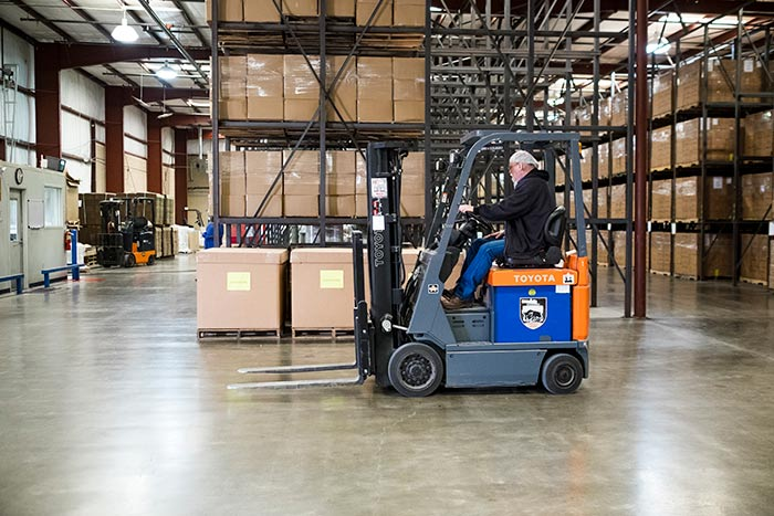 Breedlove staff operate a forklift in preparation for an aid shipment of nutritious food packs.