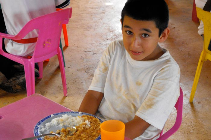 A happy young boy enjoying a nutritious meal made from Breedlove food.
