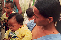 Mother with several small children in jungle village location.